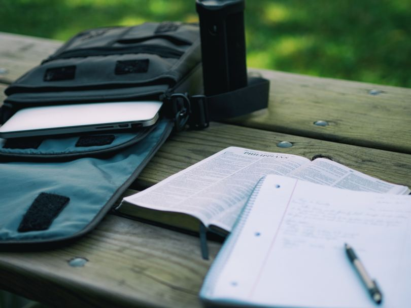 bible, notebook, and backpack on a wooden bench outside